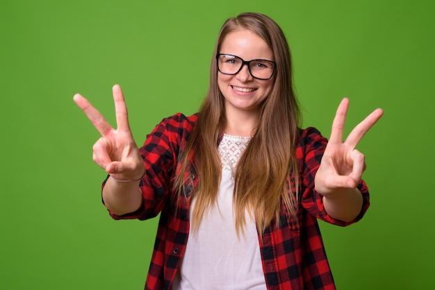 Ritratto di giovane donna bella hipster con capelli biondi sul verde