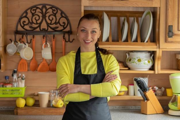 Ritratto di giovane bella casalinga in grembiule nero in piedi con le mani incrociate