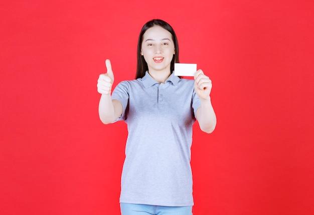 Ritratto di giovane bella signora in possesso di biglietto da visita e gesticolando pollice in alto sul muro rosso