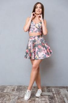 Ritratto di giovane bella donna sensuale adorabile in abito floreale estivo che le tocca il collo