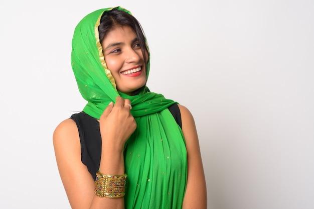 Ritratto di giovane bella donna persiana che indossa abiti tradizionali contro il muro bianco