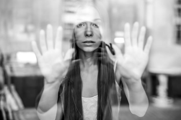 Ritratto di giovane bella ragazza bruna romantica con i capelli lunghi in posa dietro il vetro