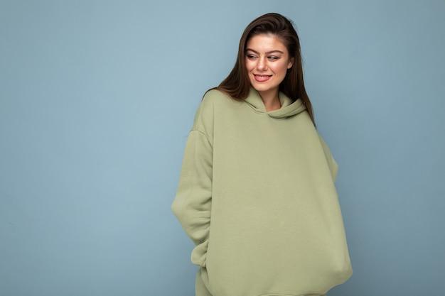 Ritratto di giovane bella ragazza sorridente in felpa con cappuccio verde hipster alla moda