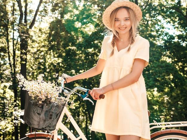 Ritratto di giovane bella ragazza sorridente hipster in prendisole estive alla moda