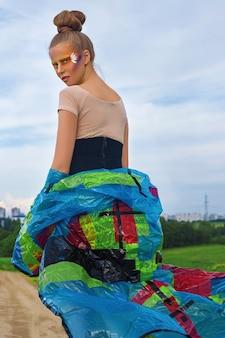 Ritratto di una giovane, bella, bianca, donna con un'acconciatura e un trucco artistico creativo, in un body e un impermeabile, in primavera, campo verde e cielo blu.