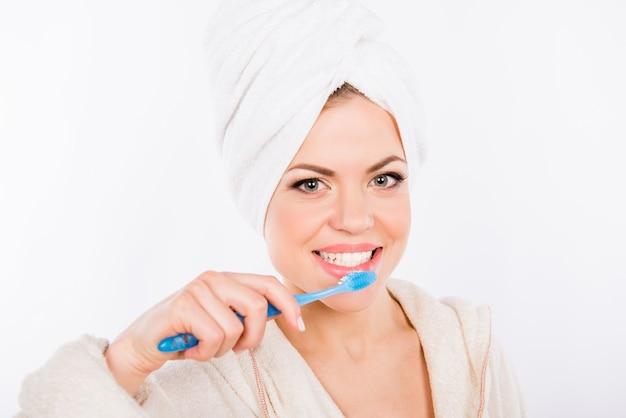 Ritratto di giovane bella donna che pulisce i suoi denti con lo spazzolino da denti