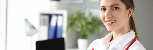 Ritratto di giovane bella dottoressa in camice bianco in ufficio