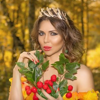 Ritratto di una giovane bella donna in un vestito fatto di foglie di autunno nel parco nella stagione autunnale con bouquet di fiori nelle sue mani. foto d'arte