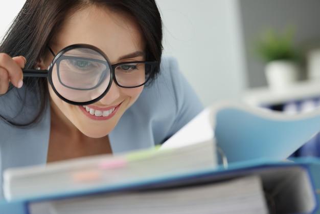 Ritratto di giovane bella donna che esamina i documenti attraverso la lente d'ingrandimento