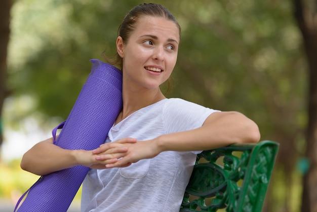 Ritratto di giovane bella donna che si esercita al parco all'aperto