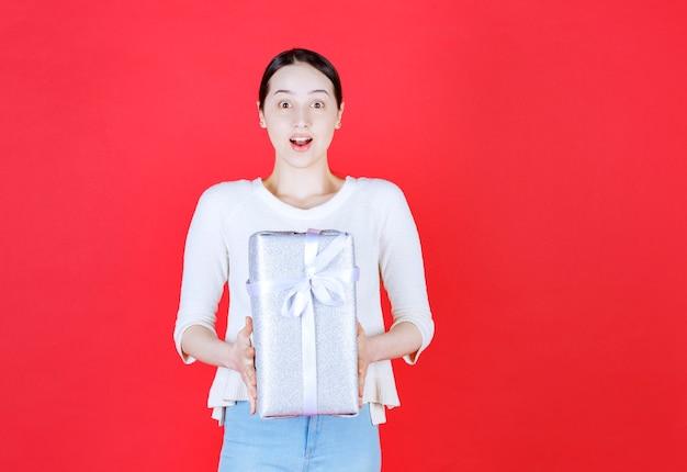 Ritratto di giovane bella donna che si sente eccitata e tiene in mano una confezione regalo