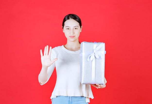Ritratto di giovane bella donna che tiene in mano una confezione regalo e che fa un gesto di stop