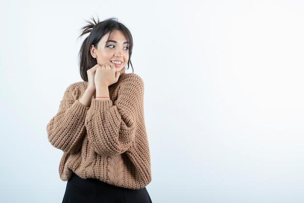 Ritratto di giovane bella donna in maglieria che mostra la faccia felice