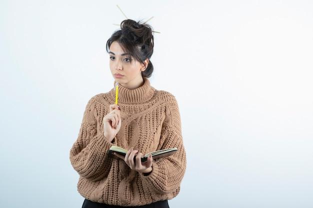 Ritratto di giovane bella donna in maglieria scrivendo qualcosa sul taccuino