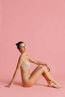 Ritratto di giovane bella donna in lingerie in posa isolata su pink