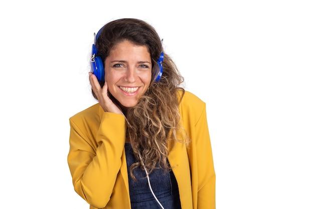 Ritratto di giovane donna bellissima, ascoltando musica con cuffie blu isolato muro bianco.