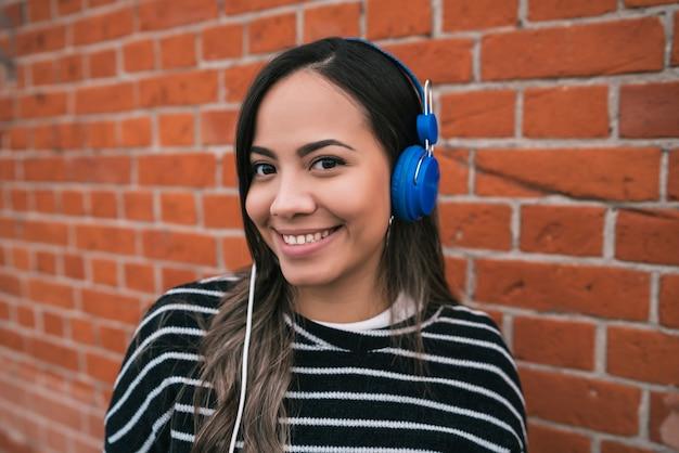 Ritratto di giovane bella donna che ascolta la musica con le cuffie blu in strada. all'aperto.