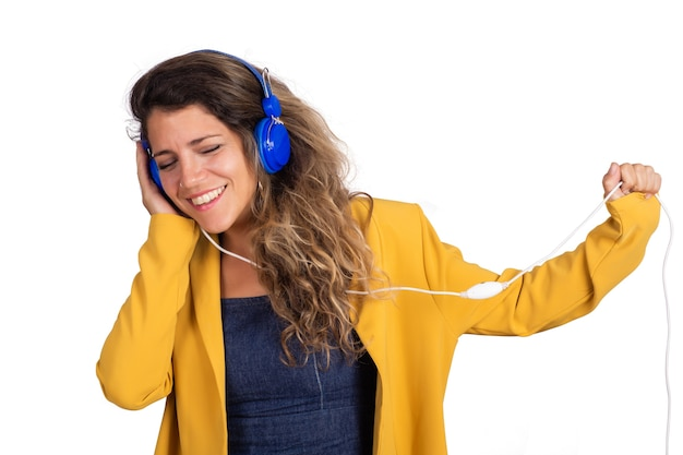 Ritratto di giovane bella donna che ascolta la musica con le cuffie blu in studio. sfondo bianco isolato.