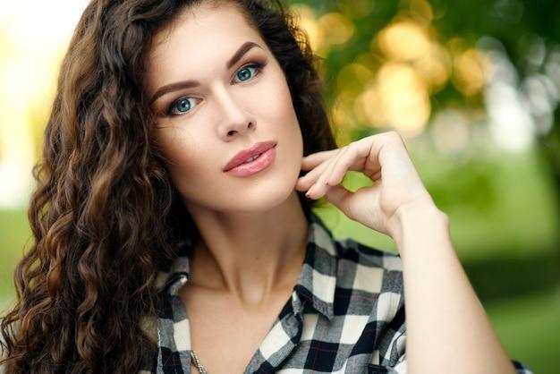 Ritratto di giovane bella donna in una camicia a quadri e capelli ricci in estate nel parco