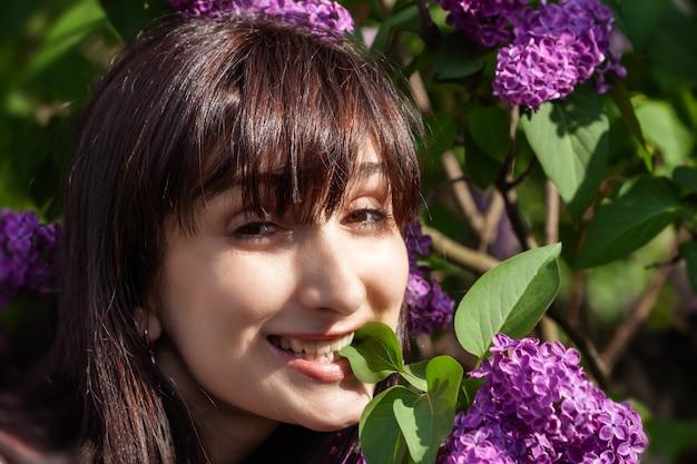 Ritratto di una giovane bella donna in posa tra i lillà in fiore. donna tra i cespugli di lillà in fiore in primavera.