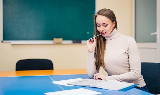Ritratto di giovane bella donna seduta in aula