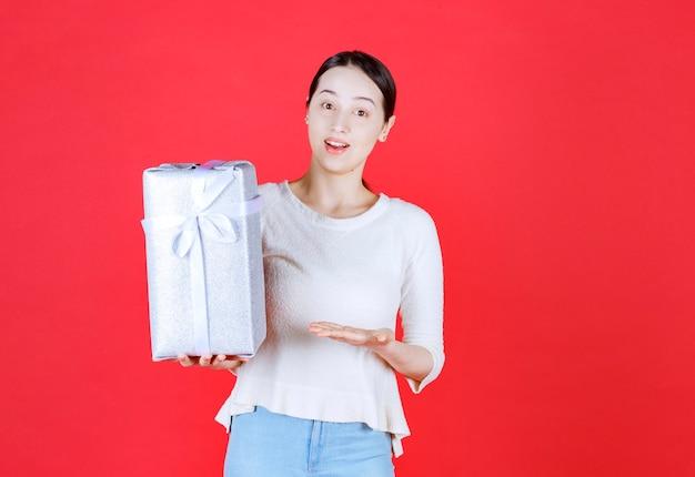 Ritratto di giovane bella donna che sorride e tiene in mano una confezione regalo
