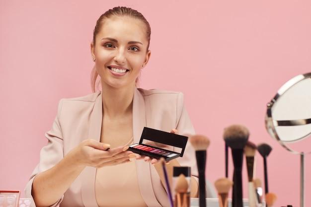Ritratto di giovane bella donna sorridente e parlando di ombretti nelle sue mani sul rosa