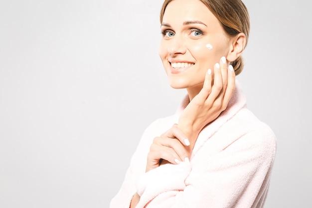 Ritratto di giovane bella donna sorridente mentre si prende un po 'di crema per il viso isolato su sfondo bianco con copia spazio.