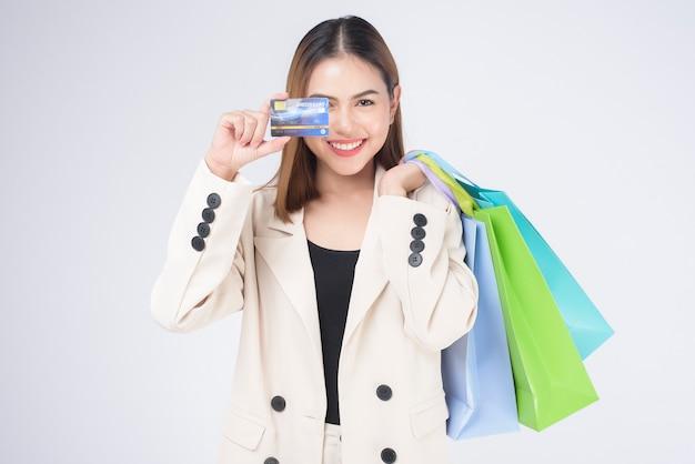 Ritratto di giovane bella donna in vestito che tiene la carta di credito sopra fondo bianco in studio