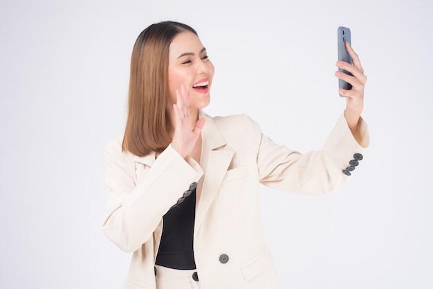 Ritratto di giovane bella donna in tuta che utilizza smart phone su sfondo bianco