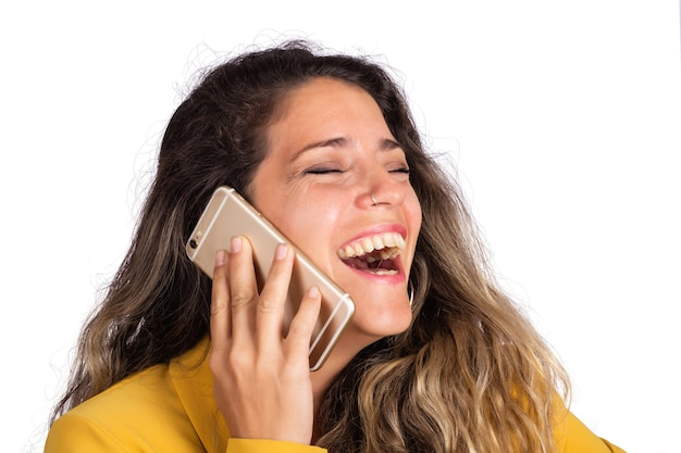 Ritratto di giovane bella donna che parla al telefono in studio. sfondo bianco isolato. concetto di comunicazione.