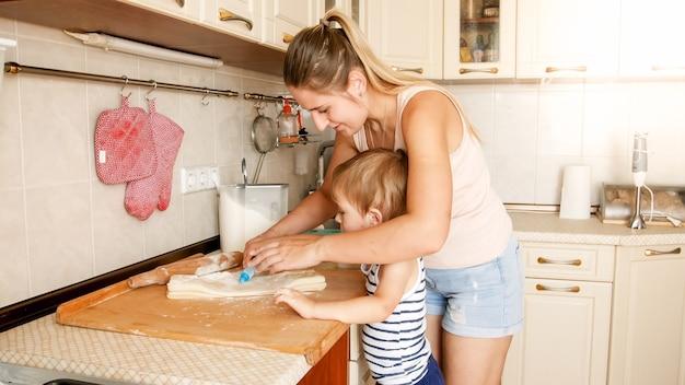 Ritratto di giovane bella donna che insegna al suo bambino a preparare biscotti e cuocere torte in cucina a casa