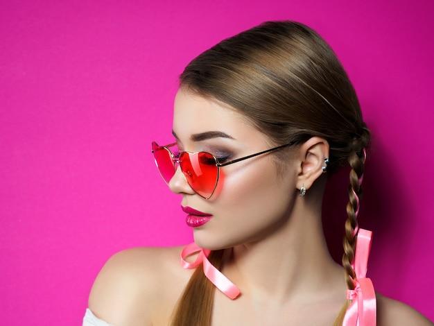 Ritratto di giovane bella donna che indossa occhiali rossi a forma di cuore. san valentino, amore o concetto di festa a tema. trucco occhi smokey e labbra rosse.