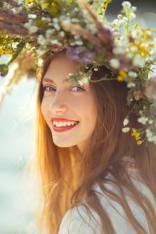 Ritratto di giovane bella donna che indossa una corona di fiori selvatici