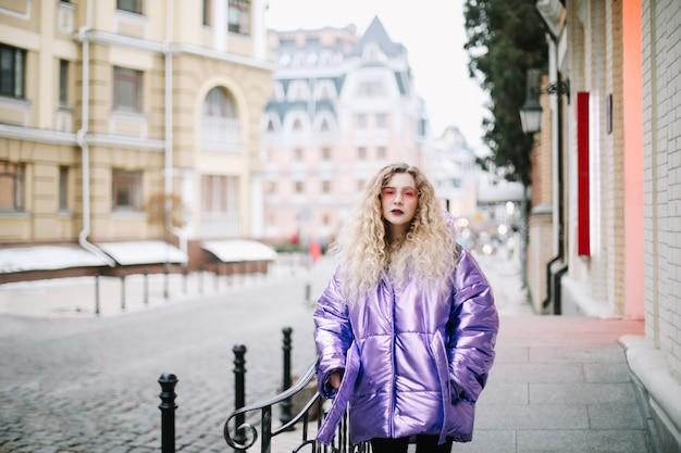 Ritratto di giovane bella donna con capelli ricci blondie all'aperto. bellezza, concetto di moda. stile di strada. sfondo bokeh