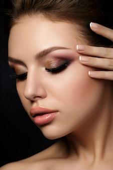 Ritratto di giovane donna bellissima con trucco sera toccando il suo viso su sfondo nero