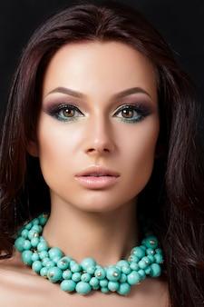 Ritratto di giovane bella donna con la sera compongono la collana blu da portare. modello in posa su sfondo scuro. occhi smokey con eyeliner. concetto di trucco classico. studio girato.