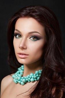 Ritratto di giovane bella donna con la sera compongono la collana blu da portare