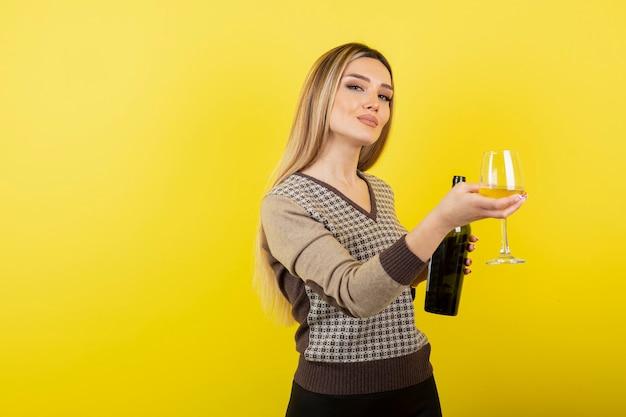 Ritratto di giovane bella donna con un bicchiere di vino bianco in posa.