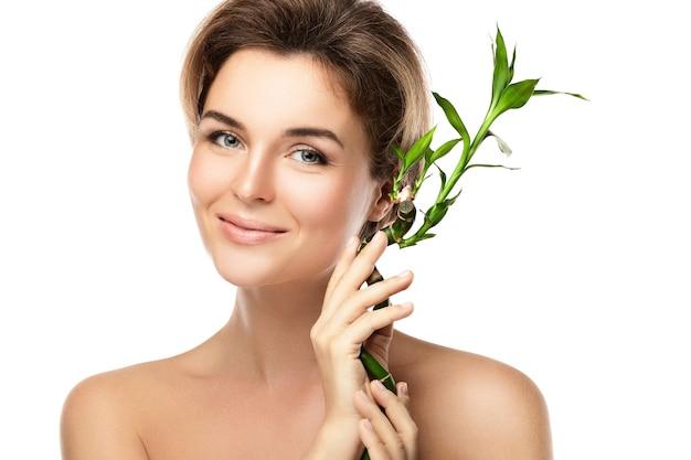 Ritratto di giovane donna bellissima con un ramo di bambù verde
