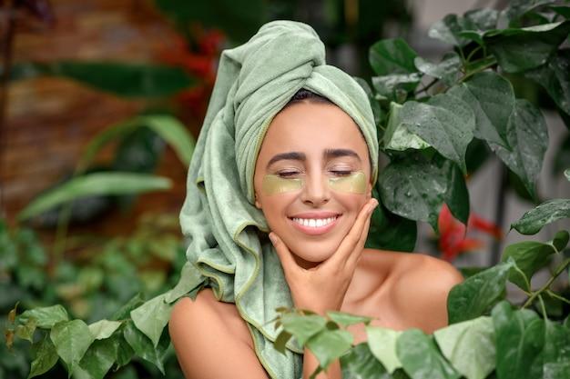 Ritratto di una giovane donna bellissima con macchie verdi sotto gli occhi e un asciugamano sulla testa.