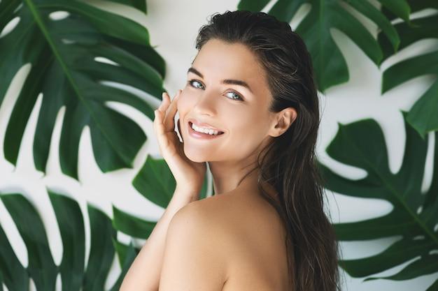 Ritratto di giovane e bella donna con perfetta pelle liscia in foglie tropicali