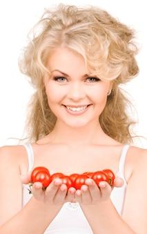 Ritratto di giovane donna bellissima con pomodori maturi