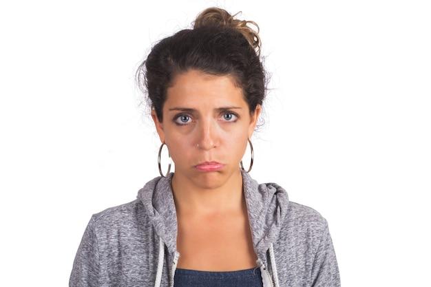Ritratto di giovane donna bellissima con espressione triste muro bianco isolato.