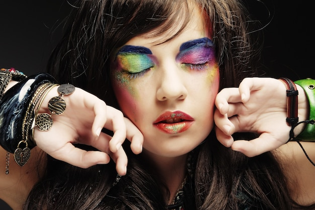 Ritratto di giovane bella donna con trucco luminoso alla moda