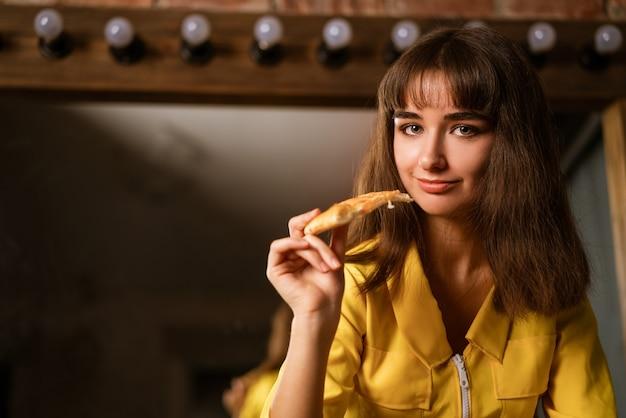Ritratto di una giovane bella donna in giallo morde un primo piano fetta di pizza