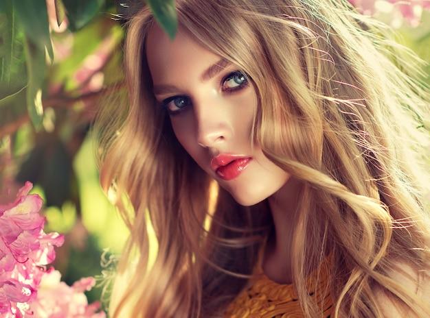 Ritratto di giovane bellissimo modello in ombra freschi alberi da giardino verde, vento leggero tra i suoi lunghi capelli biondi ricci. bellezza femminile e fiore della giovinezza. trucco e acconciatura.