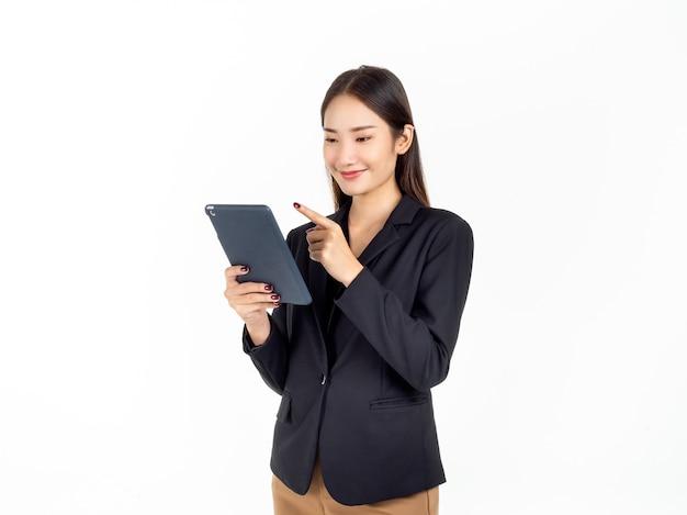 Ritratto di giovane donna di affari asiatica di bellezza in vestito nero che tiene e che punta il dito a tablet isolato