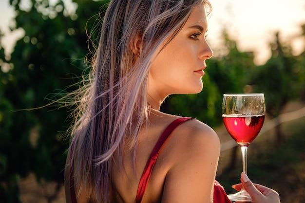 Ritratto di giovane signora di bellezza in vestito rosso nei vigneti nella stagione estiva. godendo il tour di degustazione nella meravigliosa regione vinicola.