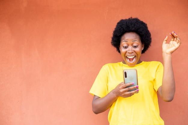 Ritratto di una giovane donna millenaria africana acconciatura afro nera con il trucco che tiene il suo telefono cellulare eccitato